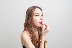 ritratto bella donna trucco e usando rossetto rosso foto