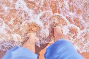 i piedi degli uomini sulla spiaggia foto