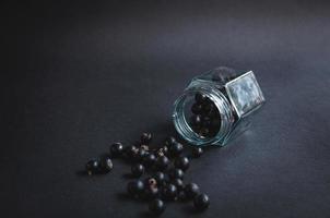 vaso di vetro con bacche di ribes su sfondo nero. foto