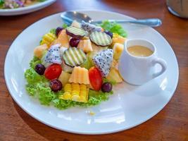 insalata di verdure su un piatto bianco posto su uno sfondo di legno. foto