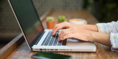 chiuda sulle mani della donna che digitano computer portatile sulla tavola di legno. foto