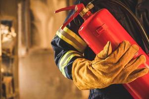 primo piano mano pompiere, pompiere che tiene l'estintore. foto