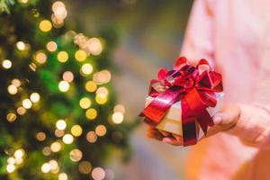 mani che tengono la confezione regalo. concetto di felicità, natale o capodanno. foto