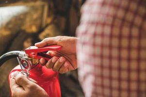 Vigile del fuoco a mano ravvicinata che usa un estintore foto