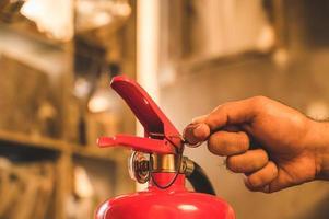 primo piano mano pompiere utilizzando estintore combattimento. foto