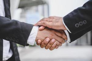 gli uomini d'affari si stringono la mano per fare affari foto