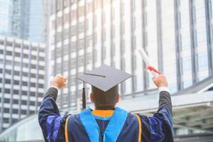 felice laureato. felice asain uomo in abiti da laurea in possesso di diploma foto