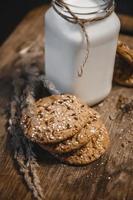 biscotti ai cereali con una brocca di latte su uno sfondo di legno. foto