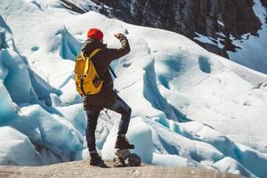 uomo viaggiatore in piedi su una roccia sullo sfondo di un ghiacciaio foto