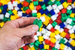 mano con mattoncini di plastica colorati su uno sfondo colorato foto