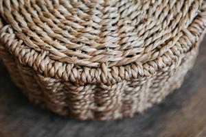 elemento di un cesto di vimini rotondo su uno sfondo di legno foto