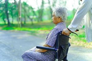 aiutare e curare la donna anziana asiatica usa il camminatore nel parco. foto