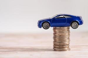 auto sulla pila di monete. prestito auto, assicurazione finanziaria e leasing foto