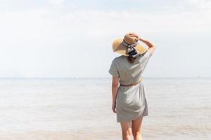 donna in abiti estivi in piedi su un molo, mare sullo sfondo foto