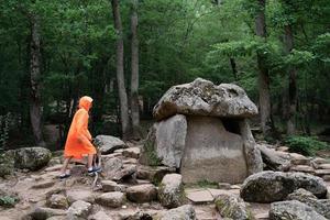 donna felice in impermeabile arancione che cammina nella foresta foto