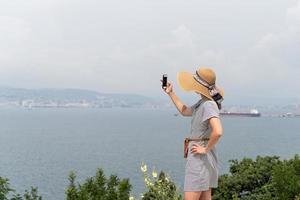 donna che fotografa il paesaggio urbano usando il cellulare foto