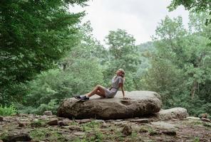 donna seduta su una grande roccia nella foresta, che riposa o medita foto