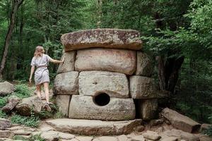 donna in abito estivo che cammina vicino a una grande pietra dolmen nella foresta foto