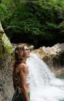 giovane donna felice che si gode la cascata foto