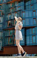 donna in abito estivo e cappello in piedi di fronte a un ufficio moderno foto