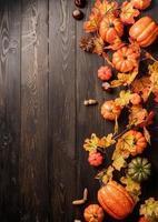 decorazioni autunnali con zucche e foglie vista dall'alto su legno nero foto