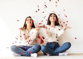 due migliori amici che si divertono a casa a soffiare coriandoli rossi foto