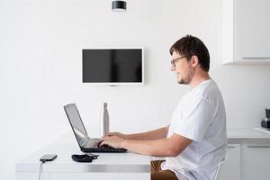 giovane uomo sorridente che lavora con il laptop da casa? foto