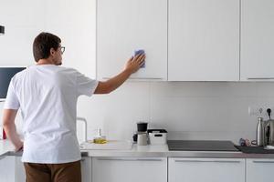 uomo che pulisce le superfici della cucina foto