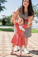 felice famiglia multirazziale di madre e figlia che camminano nel parco foto