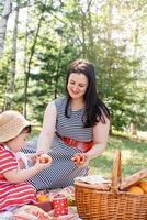 famiglia interrazziale di madre e figlia nel parco che fanno un picnic foto