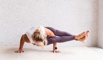 giovane donna attraente che pratica yoga, indossando abbigliamento sportivo, foto