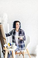 donna creativa con i capelli tinti di blu che dipingono nel suo studio foto