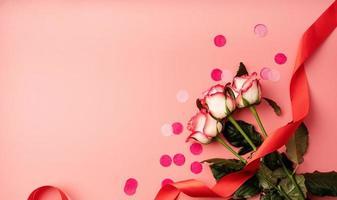 rose rosa con coriandoli su sfondo rosa a tinta unita foto