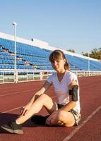 ragazza adolescente seduta sulla pista dello stadio che si riposa foto