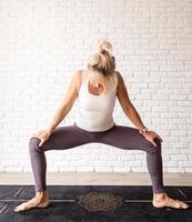 donna bionda che pratica yoga a casa foto
