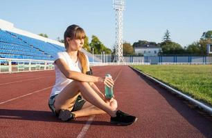 ragazza adolescente seduta sulla pista dello stadio che riposa acqua potabile foto
