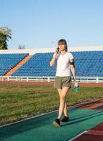 giovane donna sportiva che parla al telefono allo stadio foto