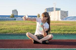 ragazza adolescente che fa selfie allo stadio dopo l'allenamento con acqua potabile foto