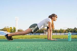 allenamento di una ragazza adolescente in piedi in una posizione di plancia allo stadio foto