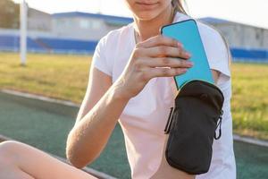 ragazza adolescente allo stadio che mette il cellulare in tasca foto