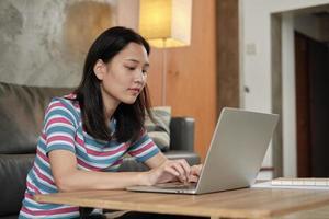 donna asiatica che utilizza laptop per lavoro da casa e apprendimento online. foto