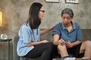 medico femminile che controlla la salute del paziente maschio anziano asiatico a casa. foto