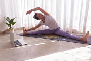 giovane donna che si allunga sul suo tappetino da yoga foto
