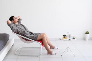 uomo seduto in accappatoio che prepara il tè a casa foto