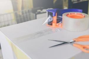 preparazione del pacco per la spedizione con forbici e taglierina per nastro adesivo. foto