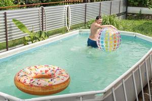 uomo che si diverte in piscina, gioca con un pallone gonfiabile foto