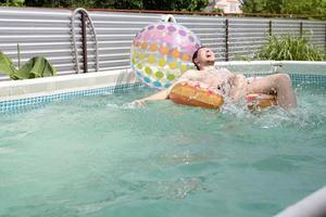 giovane che si diverte in piscina sul tubo gonfiabile da bagno foto