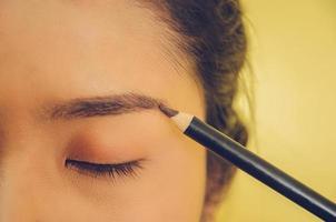 volto di bellezza della donna asiatica applicando la matita per sopracciglia sulla pelle. foto