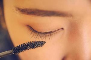 volto di bellezza della donna applicando il mascara sugli occhi dai cosmetici. foto