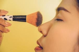 volto di bellezza della donna asiatica applicando i pennelli sulla pelle dai cosmetici. foto